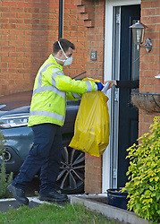 © Licensed to London News Pictures 02/02/2021.        Maidstone, UK. Firefighters collecting completed tests. Door to door testing for the South African variant of Covid-19 has started in the Maidstone area of Kent this afternoon. Police, Fire and NHS staff along with volunteers from Kent Search and Rescue and Kent County Council are handing out PCR tests to residents than collecting them an hour later. Photo credit:Grant Falvey/LNP