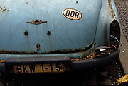 "Detail of a rusty Wartburg 312 car standing at the kerbside in an eastern Berlin district. A sticker with the letters DDR as the German Democratic Republic (DDR in German and GDR in English) as East Germany was called during the Cold War. Any car was a highly-prized possession when ownership of luxury goods like vehicles aroused suspicion for other than Communist Party officials. This car may have been someone of rank or influence. The GDR was a self-declared socialist state, referred to in the West as a ""communist state"" in the Soviet Sector of occupied Germany created after the second world war and partitioned when DDR leaders built the Berlin Wall that eventually segregated Germany and Europe. The East Germany state existed from 7 October 1949 until 3 October 1990 and was a potent symbol of a divided Europe during the Cold War."