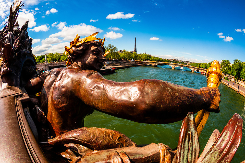 One of the Nymphs on the Pont Alexandre III over the River Seine with the Eiffel Tower in background. The bridge is the most ornate in Paris. It is in the Beaux-Arts style. Paris, France.