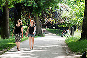 In het park Lepelenburg in Utrecht lopen twee meisjes genietend van de zon te praten in zomerse kleding.<br /> <br /> In park Lepelenburg in Utrecht two girls are walking while enjoying the sun.