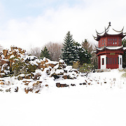 A Chinese pagoda in the snow in the Chinese Garden of the Montréal Botanical Gardens in winter. The Chinese Garden features a number of buildings and water features evocative of traditional Chinese landscaping and architecture.