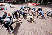 Studenten wringen zich op het Domplein in Utrecht in allerlei bochten voor een opdracht tijdens de introductieweek. Vandaag zijn in Utrecht de introductiedagen, onder de noemer UIT, van start gegaan. Eerstejaars studenten maken onder begeleiding van ouderejaars kennis met elkaar en de stad waar ze gaan studeren.<br /> <br /> New students are posing in a weird position at the Domplein in Utrecht during their introduction week of the Utrecht University.