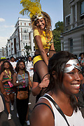 The 49th Notting Hill Carnival in West London. A celebration of West Indian / Caribbean culture and Europe's largest street party, festival and parade. Revellers come in their hundreds of thousands to have fun, dance, drink and let go in the brilliant atmosphere. Brightly coloured and feather costumes that symbolise the carnival parade. A girl sits on the shoulders of her friend.