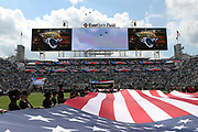 Fans hold a giant American flag during the playing of the National Anthem as military jets fly over EverBank Field stadium before the Jacksonville Jaguars 2016 NFL week 3 regular season football game against the Baltimore Ravens on Sunday, Sept. 25, 2016 in Jacksonville, Fla. The Ravens won the game 19-17. (©Paul Anthony Spinelli)