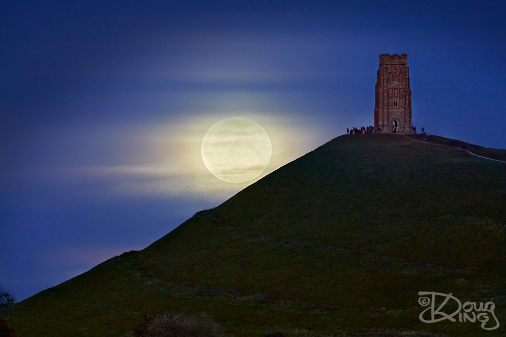 The full moon rises on Halloween 2020 veiled by thin clouds. A group of people watch it rise from beside the tower of St Michaels Church on Glastonbury Tor.