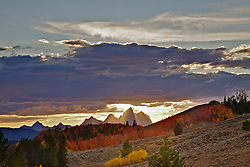 Light beams shoot through the thunder clouds illuminating the Grand Tetons on a fine fall evening in Jackson Hole Wyoming