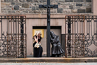 Confession time at the Old St. Patrick's Cathedral on Mulberry St. as Padré Pio (in a sculpture by Christian Master Sculptor Timothy P. Schmalz seems to listen to a lady speaking into her phone.