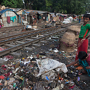 Life in the slums by the  railway tracks in Tejgaon. Homes are build closely to the tracks leading in and out of one of Dhaka's main train stations and life is goes on as in any othr part of Dhaka in spite of the dangerous proximity to the live tracks and trains passing at regular intervals. Youths looking through rubbishin search of useful scraps.