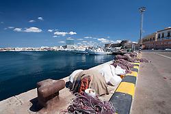 Banchina del Porto Mercantile di Gallipoli (LE) affollata dalle reti dei pescatori. Nei giorni festivi le paranza orrmeggiate in fila offrono una spettacolo notevole mentre sullo sfondo svetta il grattacielo.