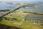 Nederland, Noord-Brabant, Willemstad, 04-03-2008; Volkeraksluizen, in de voorgrond de schutsluizen met drie kolken, daarachter, onder de brug van de A 29, de spuisluizen; dan de jachthavenmet een vierde sluis, voor de pleziervaart; op het Knooppunt Hellegatsplein splitst de snelweg, naar links de N 59, naar Goeree-Overflakkee via de Hellegatsdam, naar rechts de A29 naar de Haringvlietbrug; de Volkeraksluizen - in de Volkerakdam - verbinden het Hollandsch Diep met het Volkerak; .spuisluizen, spuien, schutten, schutsluis, sluiskolk. .luchtfoto (toeslag); aerial photo (additional fee required); .foto Siebe Swart / photo Siebe Swart.