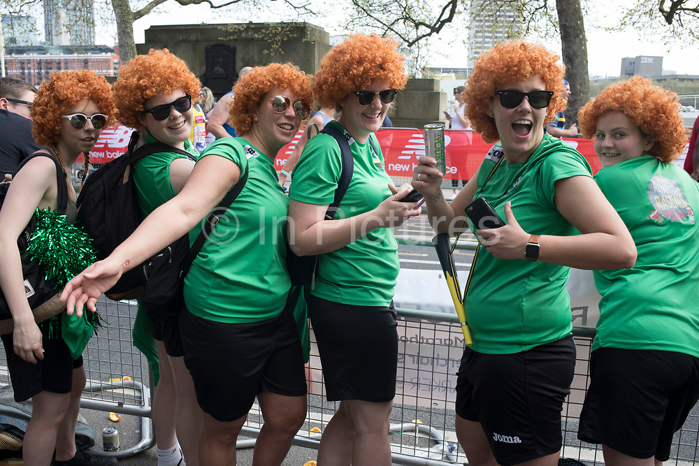 Supporters from a softball team wearing wigs encourage participants taking part in the London Marathon on 22nd April 2018 in London, England, United Kingdom. The London Marathon, presently known through sponsorship as the Virgin Money London Marathon, is a long-distance running event. The event was first run in 1981 and has been held in the spring of every year since. The race is mainly known for ebing a public race where ordinary people can challenge themsleves while raising great amounts of money for various charities.