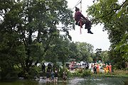 Swan, an environmental activist from HS2 Rebellion, hangs from a line secured across the shallow river Colne to an ancient alder tree in order to attempt to protect it from destruction in connection with works for the HS2 high-speed rail link on 24th July 2020 in Denham, United Kingdom. A large security operation involving officers from the Metropolitan Police, Thames Valley Police, City of London Police and Hampshire Police as well as the National Eviction Team ensured the removal of the tree by HS2 despite the protests by activists.