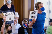 28 JUNE 2021 - DES MOINES, IOWA: Des Moines city residents listen to the mayor of Des Moines outline new guidelines for speaking at Des Moines city council meetings. Many of the city residents also objected to the new guidelines. A handful of community activists disrupted the Des Moines City Council meeting Monday. They were protesting changes in city ordinances that restricted peoples' ability to speak out at City Council meetings. They were also protesting against the city's police department's de-escalation policy, which protesters said didn't do enough to prevent police violence. One person was arrested.          PHOTO BY JACK KURTZ