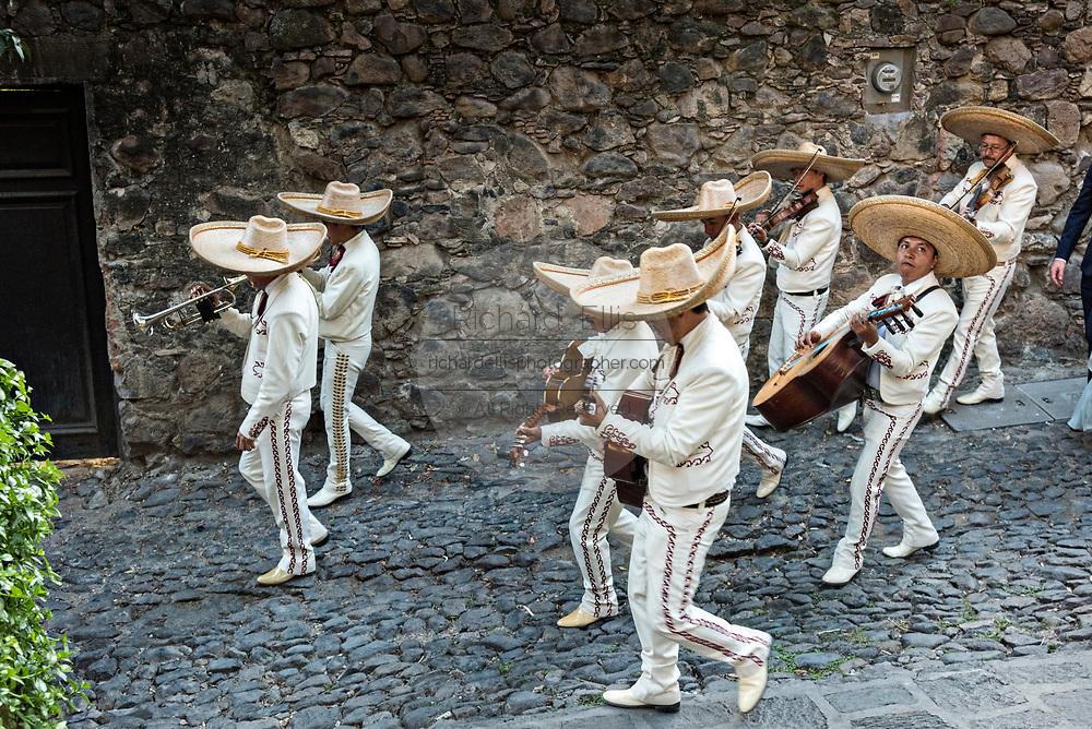 A traditional Mexican mariachi band plays during a wedding celebration parading through the streets San Miguel de Allende, Guanajuato, Mexico.