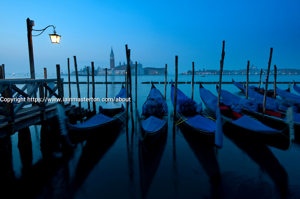 Moored gondolas at dawn on the grand canal in Venice Italy