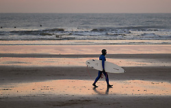 © Licensed to London News Pictures. <br /> 29/12/2014. <br /> <br /> Saltburn, United Kingdom.<br /> <br /> A surfer walks across the beach after finishing a surf at sunset on Saltburn beach as temperatures drop below freezing as the cold weather continues.<br /> <br /> Photo credit : Ian Forsyth/LNP