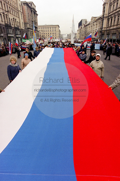 Russian citizens hold a giant Russian flag as they march in support of President Boris Yeltsin March 28, 1993 in Moscow, Russia. The supporters marched through central Moscow ending in Red Square where Yeltsin addressed the crowd.