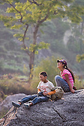 Two children laugh together on a large boulder below the village of Hille along the Annapurna Sanctuary Trek, Himalaya Mountains, Nepal.