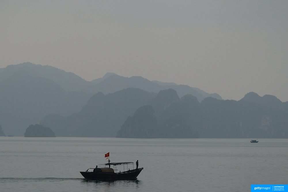 A local fisherman navigates the waters in Ha Long Bay, Vietnam. The bay consists of a dense cluster of 1,969 limestone monolithic islands. Ha Long Bay, is a UNESCO World Heritage Site, and a popular tourist destination. Ha Long, Bay, Vietnam. 11th March 2012. Photo Tim Clayton
