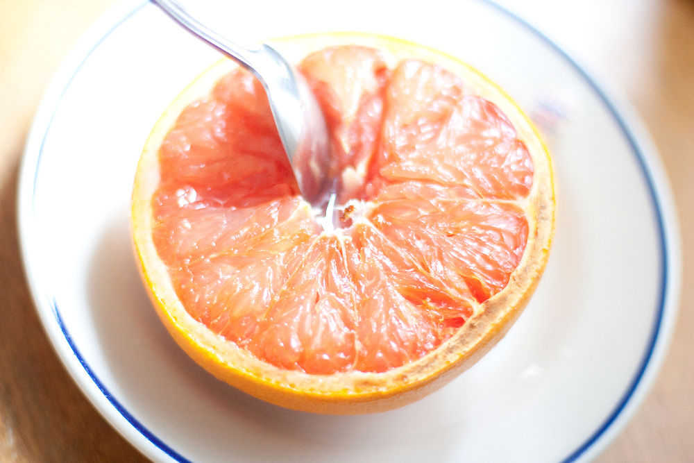 A highlight driven image of a spoon in a grapefruit half.