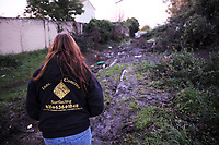 Volunteer Michelle B. walks down a muddy path toward an encampment that had been cleared out the previous week.
