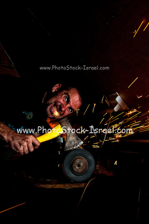 A man with a grudge grinds an axe based on the idiom Have an axe to grind (sometimes also Have an ax to grind)