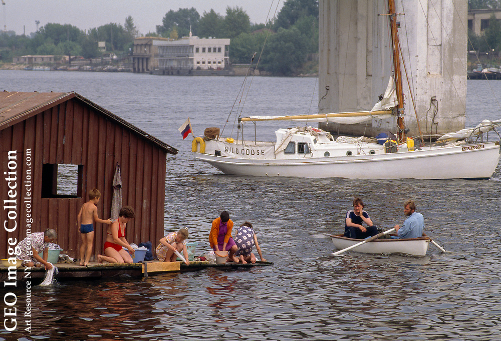 """Crewmen from the """"Wild Goose"""" row past a pier full of women in Kostroma doing l aundry in the Volga River."""