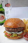 Hamburger with french fries and ketchup served with a bottle of beer