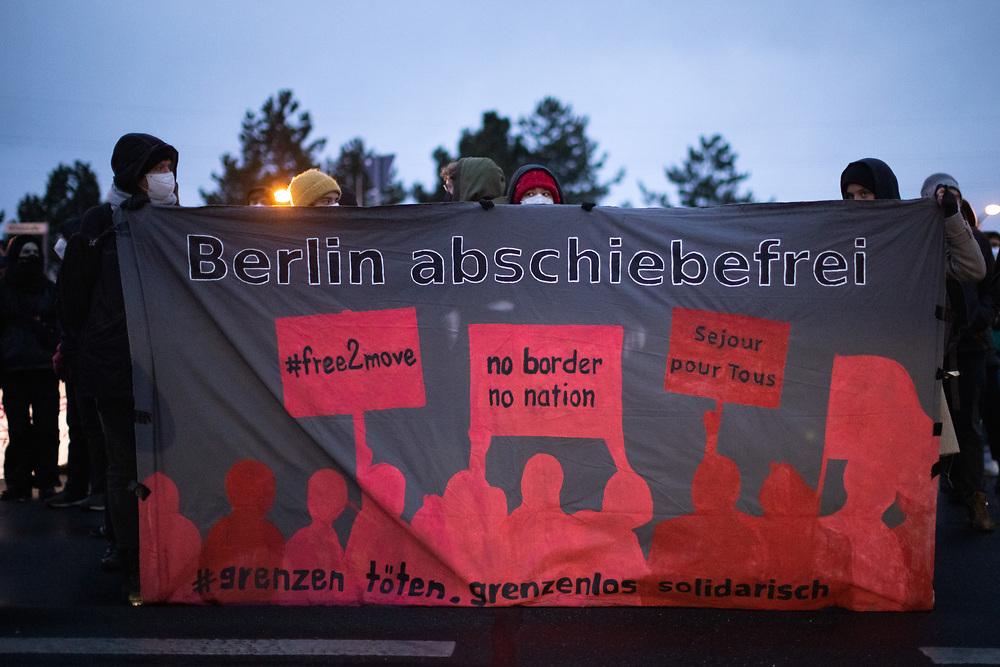 Mehrere hundert Menschen protestieren auf einer Kundgebung des Berliner Bündnisses gegen Abschiebungen am Flughafen Berlin-Brandenburg BER gegen eine geplante Sammelabschiebung nach Afghanistan. Neben der angemeldeten Kundgebung finden auch Aktionen des zivilen Ungehorsams statt. Aktivisten blockieren ein Gebäude des Abschiebegefängnisses auf dem Flughafengelände und die Mittelstraße. Vor dem Abflug laufen die Demonstranten direkt zum Zaun am Terminal 5, vor dem sie von der Polizei mit Pfefferspray gestoppt werden. Trotz Protesten und Blockadversuchen startet der Charterflug nach Kabul gegen 21:30 Uhr. Demonstranten mit Banner: Berlin abschiebefrei. Schönefeld, Deutschland, 07.04.2021.<br /> <br /> [© Christian Mang - Veroeffentlichung nur gg. Honorar (zzgl. MwSt.), Urhebervermerk und Beleg. Nur für redaktionelle Nutzung - Publication only with licence fee payment, copyright notice and voucher copy. For editorial use only - No model release. No property release. Kontakt: mail@christianmang.com.]
