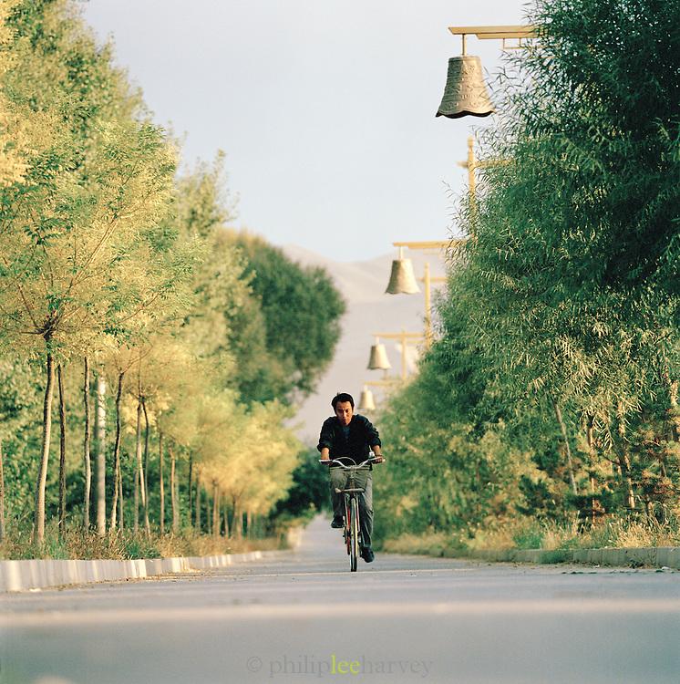 Local man riding bicycle, Silk Route, Dunhuang, Jiuquan, Gansu Province, China.