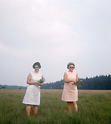Two ladies pick plants in a field on the outskirts of Brussels in the 1970s. It is overcast but their smiles are bright as the women stand for their portrait picture, taken on a film camera in 1973. Standing in ankle-deep grass in this meadow on the outskirts of the Belbian capital, they look happy with their collection of wildlife. The picture shows us a memory of nostalgia in an era from the last century.