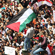 A Palestinian flag bearer mounts a traffic signal at Cairo's Tahrir Square.