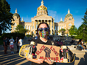 01 JUNE 2020 - DES MOINES, IOWA: A Black Lives Matter protester holds a BLM sign up with her skateboard and the Iowa State Capitol in the background. About 1,000 people gathered in front of the Iowa State Capitol in Des Moines Monday evening for a rally calling for racial justice. The rally was one week after George Floyd, an unarmed black man, was killed by a Minneapolis police officer who knelt on Floyd's back for more than eight minutes. There were protests  in Des Moines all weekend against Floyd's killing. There was some violence and some people have been arrested but the protests in Des Moines haven't been as serious as protests in other cities.         PHOTO BY JACK KURTZ
