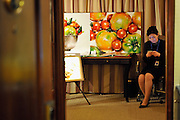 HONG KONG - MARCH 12:  An exhibitor looks at her mobile phone next to artistic work displayed as part of the Asia Contemporary Art show that takes place in the bedrooms of Conrad hotel on March 12, 2015 in Hong Kong, Hong Kong.  (Photo by Lucas Schifres/Getty Images)