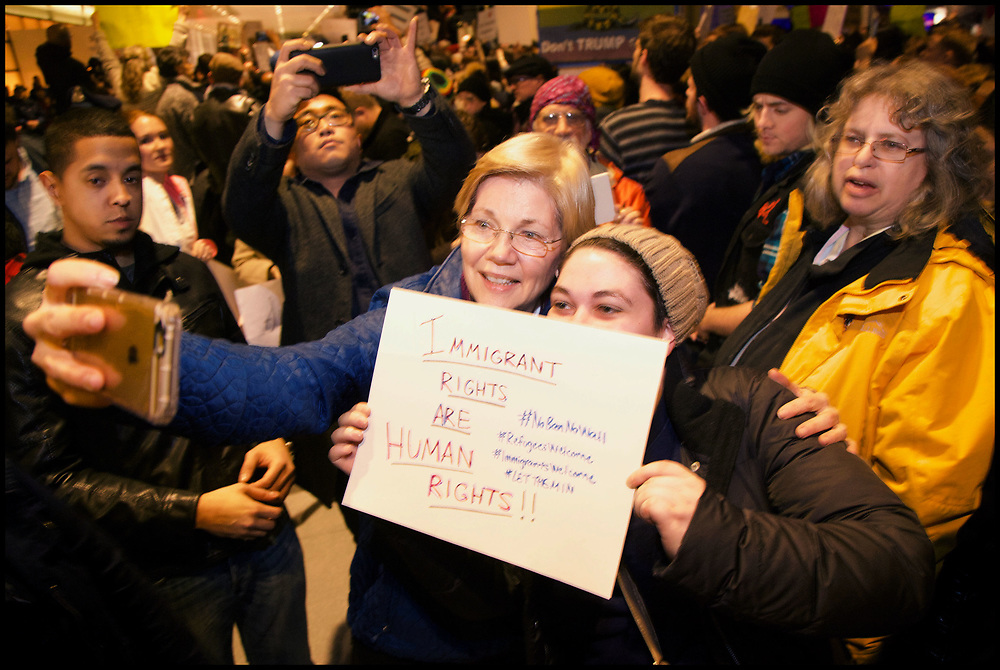 """At Boston's Logan Airport, Senator Elizabeth Warren joined hundreds of protesters assembled outside the foreign arrivals gate for hours Saturday night, chanting """"Let them in"""" as protesters gathered at airports across the nation on January 27, 2017, to demonstrate against President Donald Trump's executive order temporarily banning foreign refugees, as well as travelers from seven predominantly Muslim countries."""