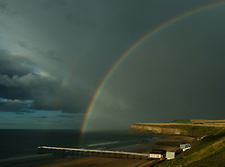 © Licensed to London News Pictures. <br /> 01/08/2017. <br /> Saltburn by the Sea, UK.  <br /> <br /> A rainbow stretches over the pier and cliffs at Saltburn by the Sea following a rain shower.<br />   <br /> Photo credit: Ian Forsyth/LNP