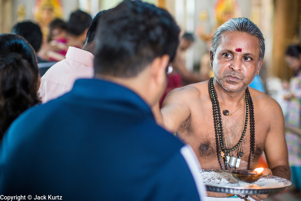22 DECEMBER 2012 - SINGAPORE, SINGAPORE:  A Hindu priest passes out blessings to Hindus in the Sri Veeramakaliamman Temple, a Hindu temple located in Little India in Singapore. The Sri Veeramakaliamman Temple is dedicated to the Hindu goddess Kali, fierce embodiment of Shakti and the god Shiva's wife, Parvati. Kali has always been popular in Bengal, the birthplace of the labourers who built this temple in 1881. Images of Kali within the temple show her wearing a garland of skulls and ripping out the insides of her victims, and Kali sharing more peaceful family moments with her sons Ganesha and Murugan. The building is constructed in the style of South Indian Tamil temples common in Tamil Nadu as opposed to the style of Northeastern Indian Kali temples in Bengal.      PHOTO BY JACK KURTZ