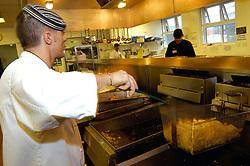 Chef prepares chips for hospital menu in NHS hospital kitchen West Yorkshire UK