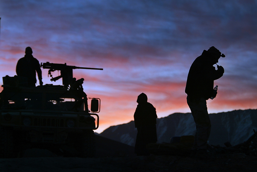 """2/23/04 -- SPECIAL FORCES A-TEAM -- ORUZGAN PROVINCE, AFGHANISTAN --  Sgt. First Class Jay Pope, 32, of Chesterton, IN, (right) brushes his teeth and Staff Sgt. Don Grambusch, 27, of Bailey, CO, left, and other members of the A-TEAM with the 3rd Special Forces Group wake up in the early morning hours while sitting on a weapons cache site disclosed to them by the Oruzgan District Tribal Chief.  The team camped for two nights in front of the district tribal chief headquarters before finally being allowed to remove the 10 tons of weapons and munitions to be destroyed. A local Afghan moves about there position in front of the district tribal chief headquarters. The ANA and the Special Forces team were able to implement their form of """"Afghan Diplomacy"""" and after two days the team was able to haul away nearly 10 tons of weapons and munitions from bunkers under the district chiefs compound. (Photo by Jack Gruber, USA TODAY)  ORG XMIT: Special Forces_jg2178"""