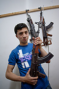 Kalashnikov assault rifles hang on the wall as a Free Syrian Army (FSA) member hold his personal rifle and pose for a picture at the FSA facilities in Marea on Monday, May 28, 2012. (Photo by Vudi Xhymshiti)