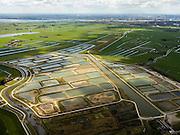 Nederland, Noord-Holland, Amsterdam (landelijk Noord), 16-04-2012; Waterland, overzicht met Volgermeerpolder, daar achter links Veenderij Zunderdorp, het water van de de Ransdorper Die en het IJsselmeer. Aan de horizon Amsterdam.De Volgermeerpolder maakte oorspronkelijk ook deel uit van de Veenderij, tot in de jaren '50 is hier turf gewonnen. Na beeindiging van het vervenen werden de 'petgaten' volgestort met huisvuil en chemisch afval, onder andere met dioxine en benzeen afkomstig van Philips-Duphar..Inmiddels is de polder gesaneerd, de voormalige vuilstortplaats is afgedekt met folie en voorzien van en afdeklagen, bestaande uit zowel grond als ook water. Het ontwerp voorziet in een natuurgebied met 'sawa's' waarin nieuw veen zich kan ontwikkelen wat de vervuilde grond verder zal isoleren (natural capping)..The Volgermeerpolder in the rural area near Amsterdam once a landfill site for heavily polluted household and industrial waste, has been cleaned up using natural capping and turned into a nature area. Skyline Amsterdam. .luchtfoto (toeslag), aerial photo (additional fee required);.copyright foto/photo Siebe Swart