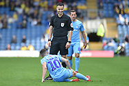 The referee has a laugh with injured Coventry City striker (on loan from Portsmouth) Conor Chaplin (10) during the EFL Sky Bet League 1 match between Oxford United and Coventry City at the Kassam Stadium, Oxford, England on 9 September 2018.