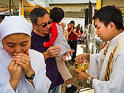 18 SEPTEMBER 2016 - BANGKOK, THAILAND:  A nun takes communion during the 100th anniversary mass at Santa Cruz Church. Santa Cruz Church was establised in 1769 to serve Portuguese soldiers in the employ of King Taksin, who reestablished the Siamese (Thai) empire after the Burmese sacked the ancient Siamese capital of Ayutthaya. The church was one of the first Catholic churches in Bangkok and is one of the most historic Catholic churches in Thailand. The first sanctuary was a simple wood and thatch structure and burned down in the 1800s. The church is in its third sanctuary and was designed in a Renaissance / Neo-Classical style. It was consecrated in September, 1916. The church, located on the Chao Phraya River, serves as a landmark for central Bangkok.      PHOTO BY JACK KURTZ