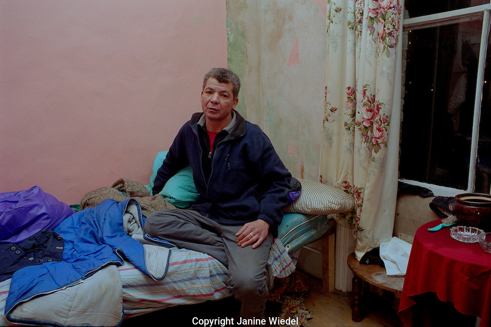Middle age man on bed in his room in St Agnes Place Squat in Kennington South London.