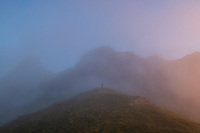 Hikker concealed in fog among mountain peaks, Moskenesøy, Lofoten Islands, Norway