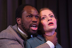 """© Licensed to London News Pictures. 15/01/2014. London, England. Stefan Adegbola as Othello and Gillian Saker as Desdemona. The Shakespearean tragedy """"Othello: The Moor of Venice"""" opens at the Riverside Studios in Hammersmith, London in a """"Film Noir"""" setting. Directed by Rebekah Fortune with Stefan Adegbola as Othello and Gillian Saker as Desdemona. Running form 15 January to 18 February 2014. Photo credit: Bettina Strenske/LNP"""