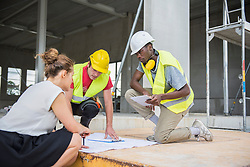 Architect discussing blueprint with construction workers at building site, Munich, Bavaria, Germany