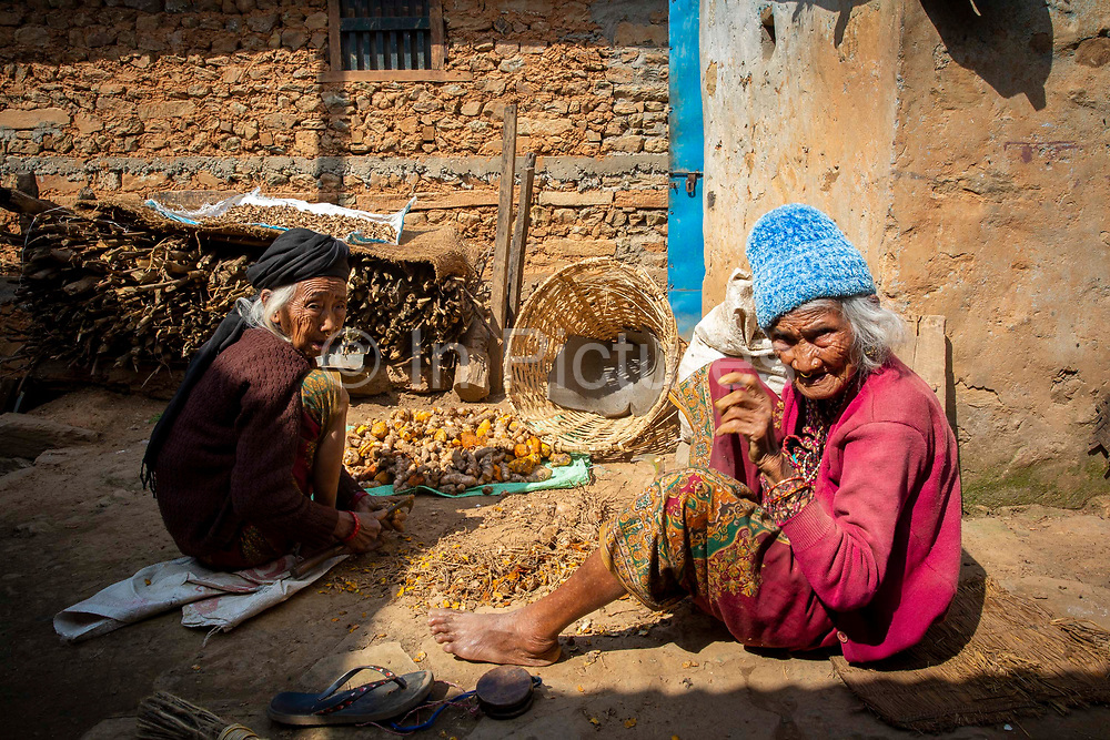 Two elderly Nepalese women sorting through their Turmeric crop on the 3rd of March 2020 in the rural mountain village of Dalbhanjyang, Ghairung, Gorkha, Nepal.