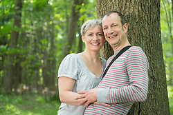 Portrait of mature couple leaning by tree in forest, smiling