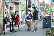 City Concierge Louisville's Laura Wallace, left, visits with Johnny Berry, center, singer with JB and the Outliers and his brother Mark Berry, visiting from Hawaii outside Market Street's Taste Fine Wines and Bourbons Saturday, April 13, 2013 in Louisville, Ky. (Photo by Brian Bohannon)
